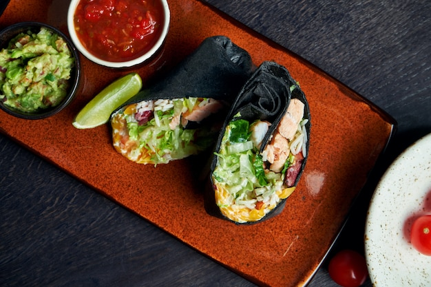 Закройте вверх по взгляду на буррито с семгами, салатом, рисом, томатами, мозолью и болгарским перцем в черном пита на коричневой плите с сальсой томата и гуакамоле. вегетарианский рулет с шаурмой