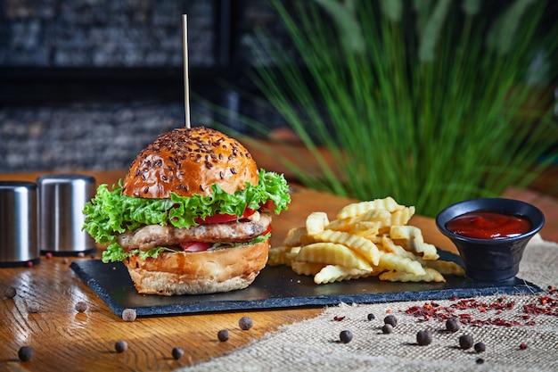 古典的なアメリカのハンバーガーのビューを閉じます。チキンバーガーとフライドポテトとレッドソース。不健康なファーストフード。コピースペースと石のプレートとロフト暗のハンバーガー。サンドイッチ