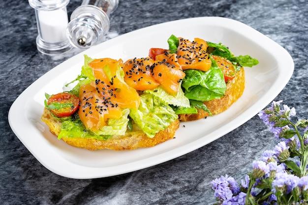 Крупным планом вид на вкусные итальянские брускетты с лососем, листьями салата, помидорами черри и соусом