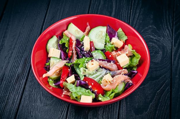 Крупным планом вид на свежий домашний салат с лососем, помидорами, огурцами, листьями салата и сыром
