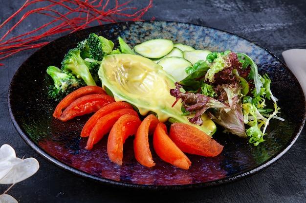 暗闇の中で黒い織り目加工のプレートで提供されているアボカドとグリーンサラダのビューを閉じます。フラットレイアウトの食品。ビーガンフレッシュサラダ。