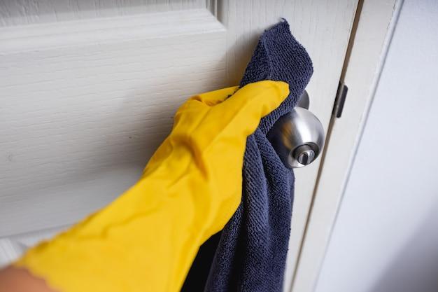 Крупным планом вид под рукой в защитных желтых перчатках, дезинфицирующих дверную ручку во время уборки дома, концепция защиты от коронавируса