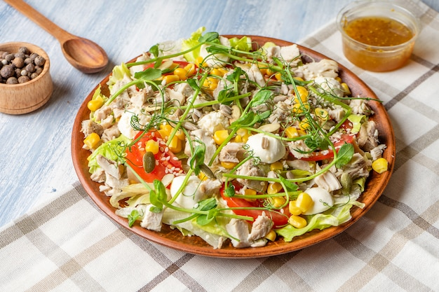 おいしいサラダの大きなプレートのビューを閉じます:トマト、フェタチーズ、ロースト肉チキン、アスパラガス、グリーン。食品写真の背景。