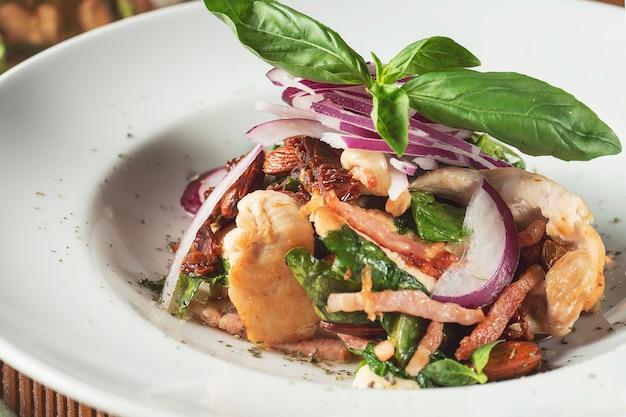 Panzanella 또는 panmolle- 담근 된 부패한 빵, 양파, 토마토 나무 배경에 inwhite 그릇의 인기있는 이탈리아 다진 된 샐러드에 뷰를 닫습니다.