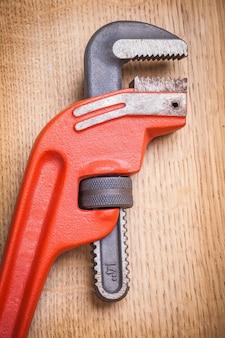 Крупным планом вид на трубный ключ на деревянной доске