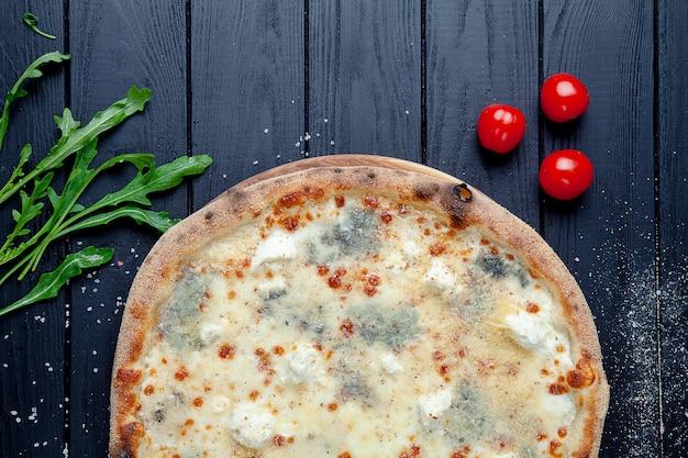 Крупным планом вид на пиццу с 4 сырами: горгонзола и пармезан. фета, моцарелла. выборочный фокус. кусочек пиццы с ингредиентами. темный фон итальянская кухня. копировать пространство