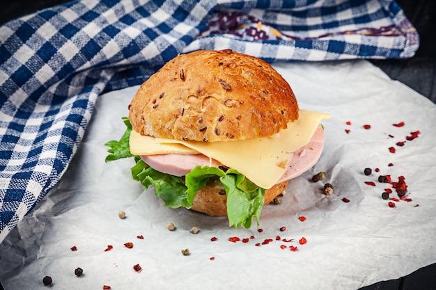 Крупным планом вид на бутерброд с ветчиной, листьями салата, помидор на белой поверхности