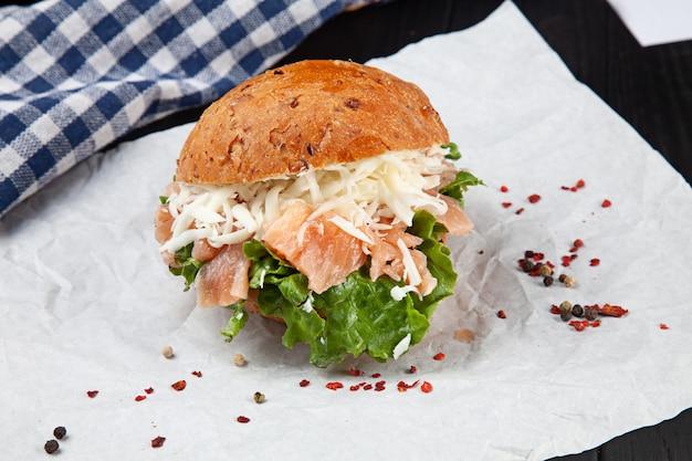 Крупным планом вид на бутерброд с лососем, листьями салата, помидор на белой поверхности