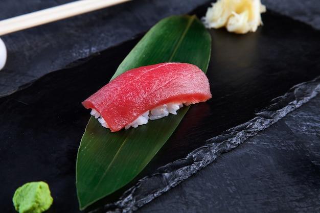 Закройте вверх по взгляду на, который служат nigiri с тунцом на темной плите на темной предпосылке с космосом экземпляра. вкусный лосось нигири суши.