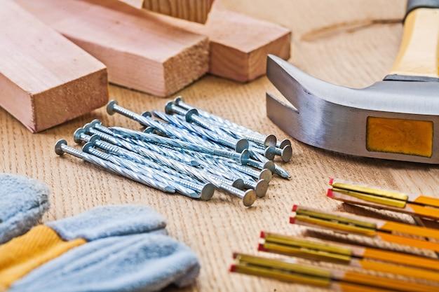 Крупным планом вид на набор столярных инструментов молоток гвоздей перчатка метр доски на деревянной доске
