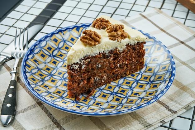 白いテーブルの上の青いセラミックプレートにクリームとナッツのキャロットケーキのスライスのビューを閉じます。ヘルシーなデザート。