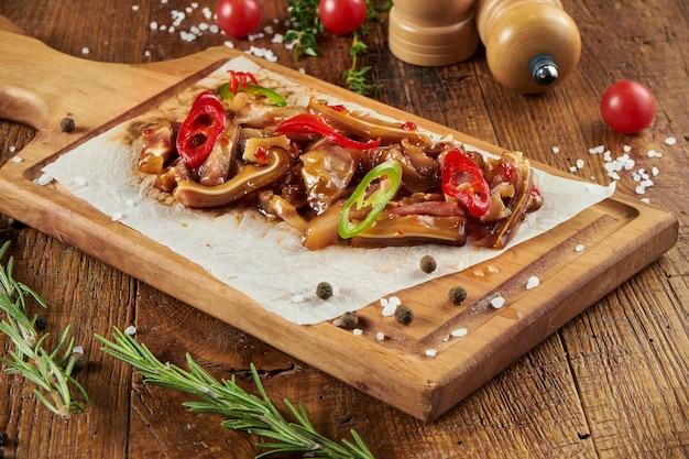 スパイスと組成の木製の表面の羊皮紙に唐辛子と甘酸っぱいソースのスモーク豚の耳のビューをクローズアップ