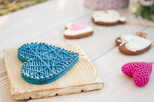 ストリングアートとかぎ針編みのハート型の結婚式の装飾のクローズアップビュー。スティックにハート型のクッキー。