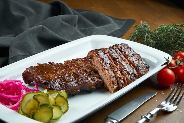 Закройте вверх по взгляду на вкусных очень вкусных нервюрах сваренных барбекю с соусом барбекю в белой плите на деревянном столе. классическая американская свинина барбекю в составе с ингредиентами