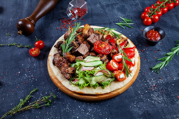 그루지야 어 피타에 야채와 함께 맛있는 구운 된 고기에보기를 닫습니다. 피타에 shashlik 또는 바베큐 고기. 전통 그루지야 요리 음식 시시 케밥. 디자인을위한 공간을 복사하십시오. 어두운 배경