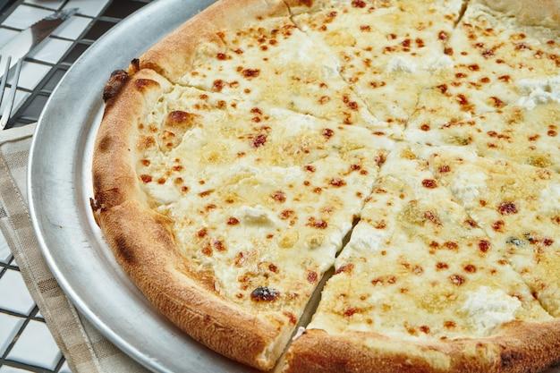 Закройте вверх по взгляду на вкусной домодельной итальянской пицце 4 сыров в составе с специями и томатами вишни на белой таблице. вид сверху. еда плоская планировка