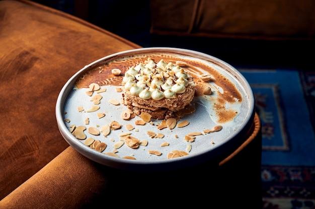 ヘーゼルナッツ、チョコレートグレーズ、バタークリームのような詰め物が入った2層のメレンゲから作られたキエフケーキを提供するおいしいレストランのクローズアップビュー。白い皿の上のケーキ
