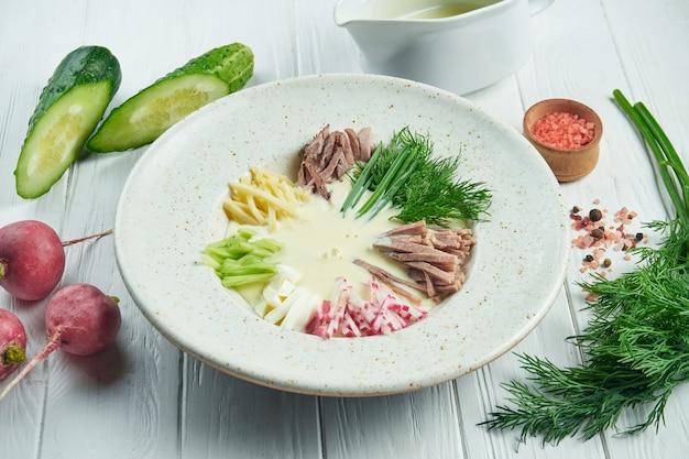 肉、発酵焼きミルク、キュウリ、大根、卵、木製の背景に白い皿にサーとおいしいロシアのオクローシカスープのビューをクローズアップ