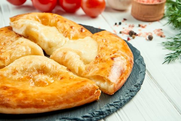 おいしい伝統的なカチャプリ-溶けた塩チーズ(スルグニ)を詰めた閉じた焼きパイのビューを閉じます。グルジア料理