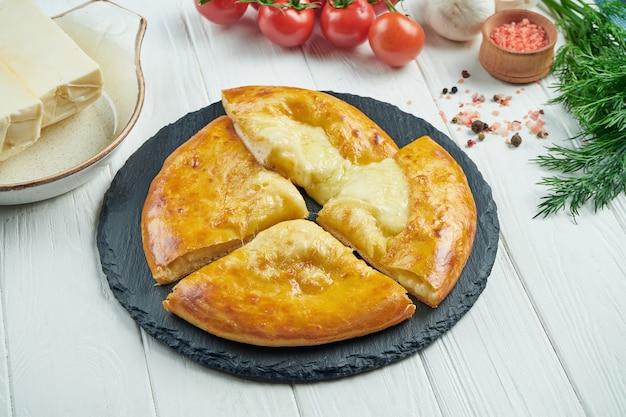 おいしい伝統的なカチャプリのビューを閉じます-黒のトレイに溶かした塩チーズ(スルグニ)または肉を詰めた焼きたてのパイ。伝統的なグルジア料理