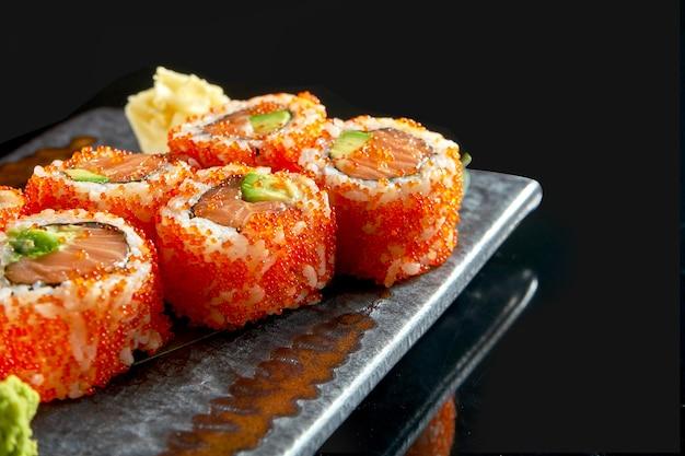 サーモン、アボカド、トビコキャビアを添えたおいしいウラマキのクローズアップ。日本の伝統料理。食品デリバリー。黒で隔離