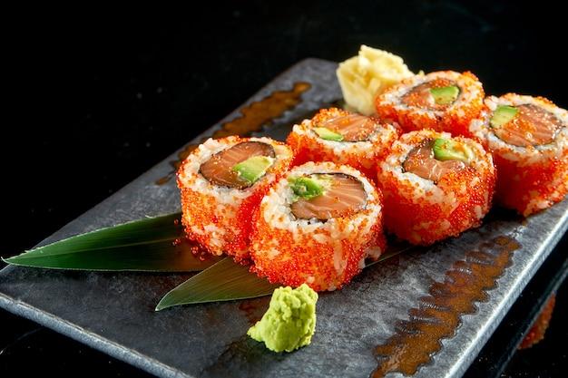 Крупным планом вид вкусные урамаки с лососем, авокадо и икрой тобико. японская традиционная кухня. доставка еды. изолированные на черном