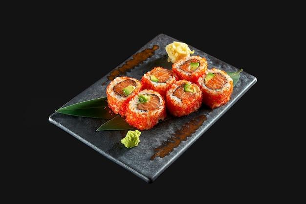 Крупным планом вид вкусных урамаки с лососем, авокадо и икрой тобико