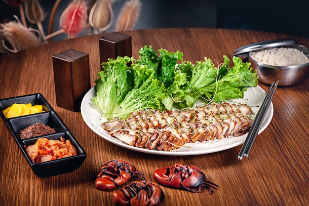 レタスの葉と甘酸っぱいソースで伝統的な韓国スライスポークのビューを閉じます。キムチを添えた肉。コピースペース付きの韓国料理。食品の背景。