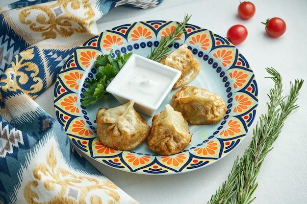Крупным планом вид на традиционные турецкие манты манлама, фаршированные фаршем с йогуртом и томатным соусом в тарелке на белой поверхности. манти