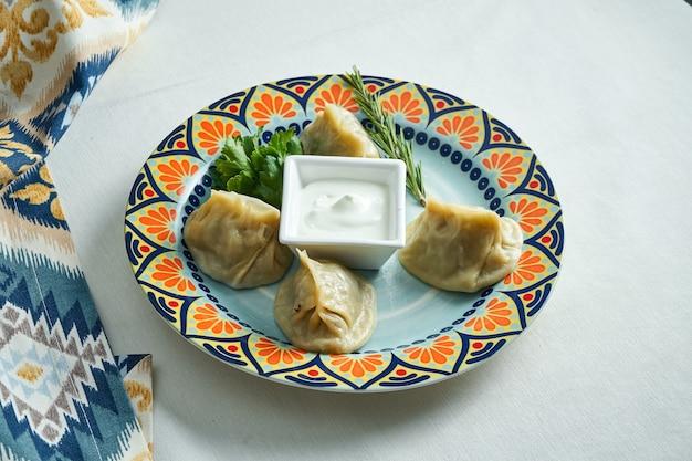 Крупным планом вид на традиционные турецкие манты манлама, фаршированные мясным фаршем с йогуртом и томатным соусом, в тарелке на белом