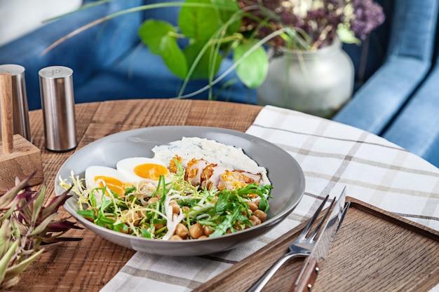 木製のテーブルの上にボウルでお召し上がりいただけますヒヨコ豆の七面鳥のサラダのクローズアップ表示