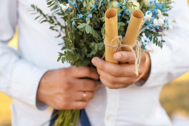 Крупным планом вид на два свернутых бумажных листа со свадебными клятвами в руке жениха