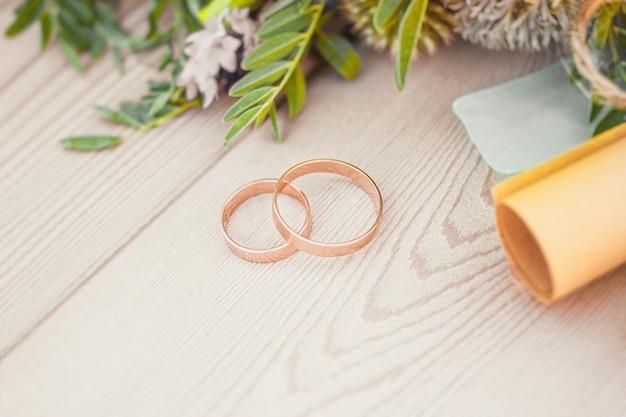 結婚指輪と結婚式の誓いと花束の装飾が施された2枚のロール紙のクローズアップビュー
