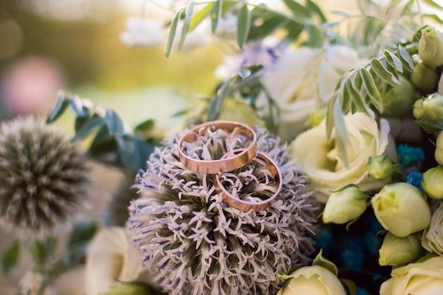 Крупным планом вид на обручальные кольца на букет невесты в деревенском стиле.