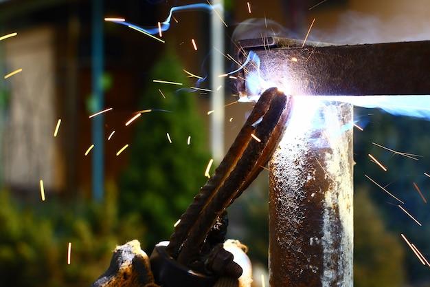 周りに火花が付いた錆びた金属フレームの溶接の拡大図。