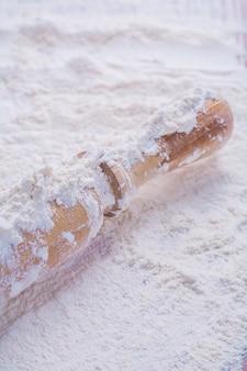 白い天然小麦粉の食べ物や飲み物のコンセプトに木製の麺棒のビューをクローズアップ