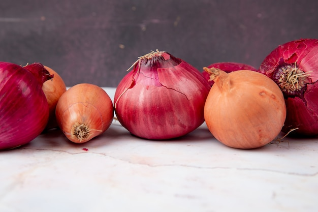 Close-up view of onions on white surface and maroon background