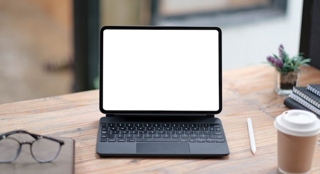 Close-up view of open blank screen laptop computer with office supplies in modern office
