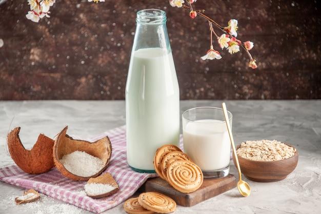 Vista ravvicinata della bottiglia di vetro aperta e della tazza piena di avena di biscotti con cucchiaio di latte in vaso marrone su asciugamano spogliato viola su tagliere di legno
