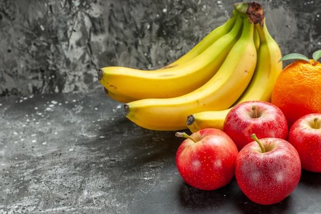Vista ravvicinata della fonte di nutrizione organica fascio di banane fresche e mele rosse un'arancia su sfondo scuro