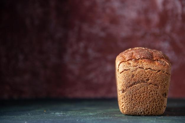 Vista ravvicinata del pane nero confezionato sul lato sinistro su sfondo marrone in difficoltà con spazio libero