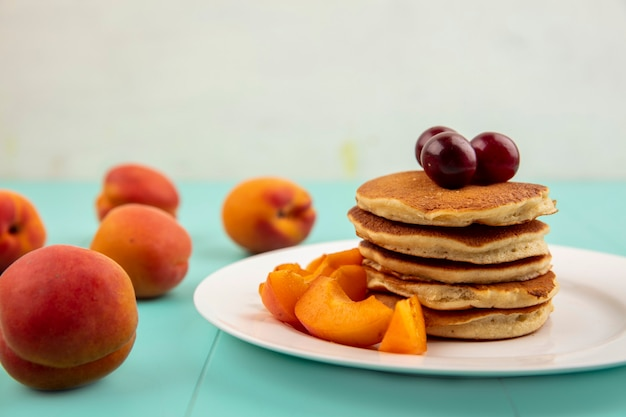 Close-up view of pancakes with apricot slices and cherries in plate and apricots on blue surface and white background