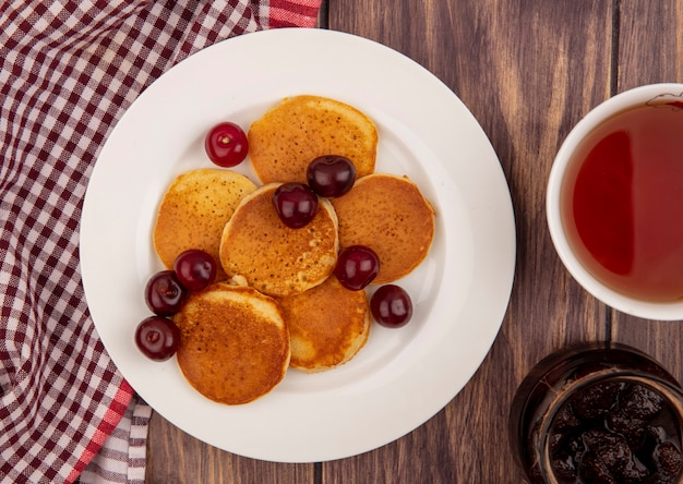 Close-up view of pancakes with cherries in plate on plaid cloth with cup of tea and strawberry jam on wooden background