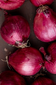 Close-up view of pattern of red onions on maroon background