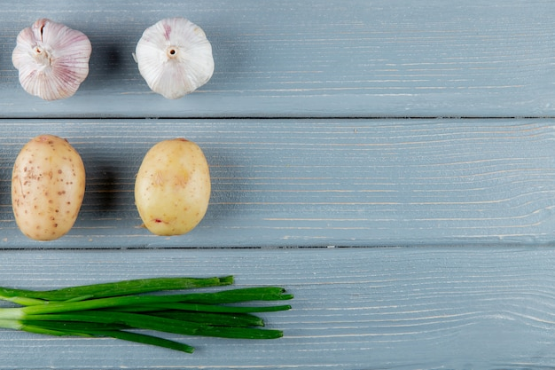 Close up view of pattern of vegetables as garlic potato and green onion on wooden background with copy space