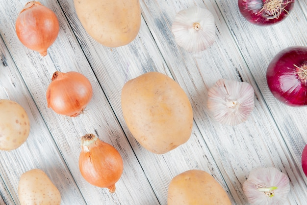 Close up view of pattern of vegetables as onion garlic potato on wooden background