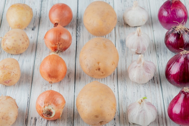 Close up view of pattern of vegetables as onion potato garlic on wooden background