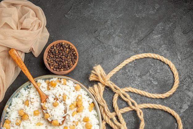 Vista ravvicinata di piselli e piatto di riso con un cucchiaio e pepe in una ciotola e una corda sul buio