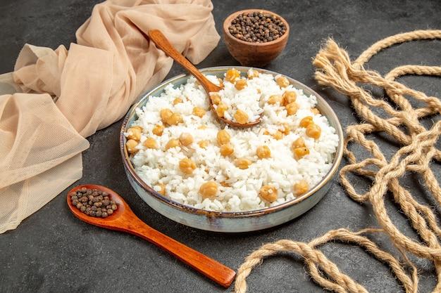 Vista ravvicinata di piselli e piatto di riso con un cucchiaio e pepe in una ciotola e cucchiaio sul buio