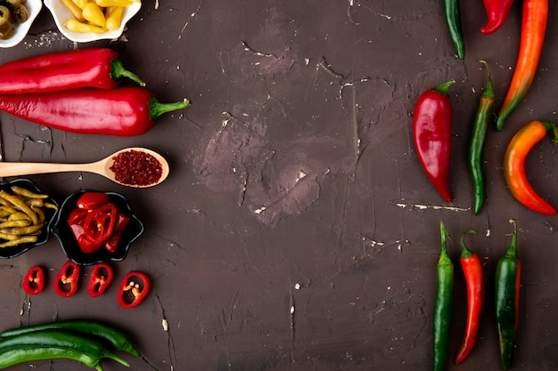 Close-up view of peppers with sumac and salted pepper on maroon background with copy space